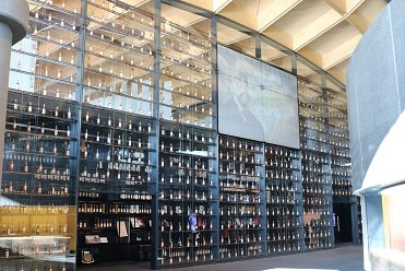 Full large glass wall with integrated whiskey bottle display case